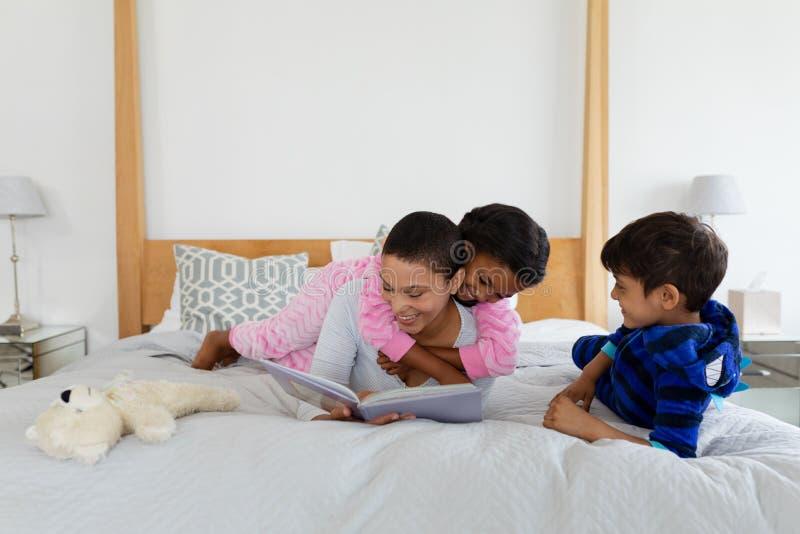 Mãe e crianças que têm o divertimento ao ler um livro da história no quarto fotografia de stock royalty free