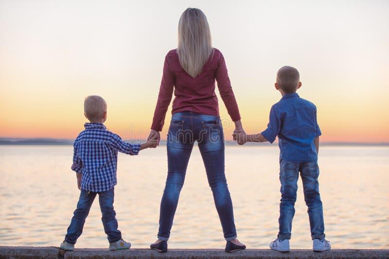 A mãe e dois filhos andam no passeio e olham o por do sol foto de stock