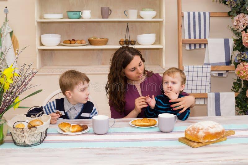 Mãe e duas crianças na cozinha fotos de stock royalty free