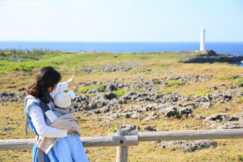 Mãe e ele asiáticos bebê na viagem da família no parque de beira-mar de Zanpa em Okinawa foto de stock royalty free