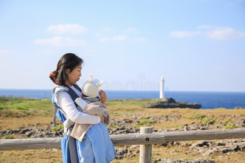 Mãe e ele asiáticos bebê na viagem da família no parque de beira-mar de Zanpa em Okinawa fotografia de stock