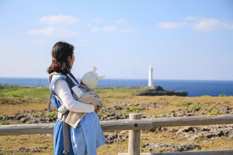 Mãe e ele asiáticos bebê na viagem da família no parque de beira-mar de Zanpa em Okinawa foto de stock