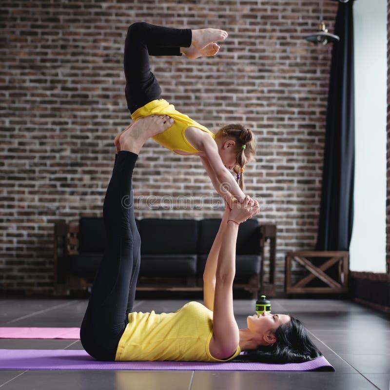 Mãe e exercícios ginásticos daughterdoing junto em casa fotografia de stock