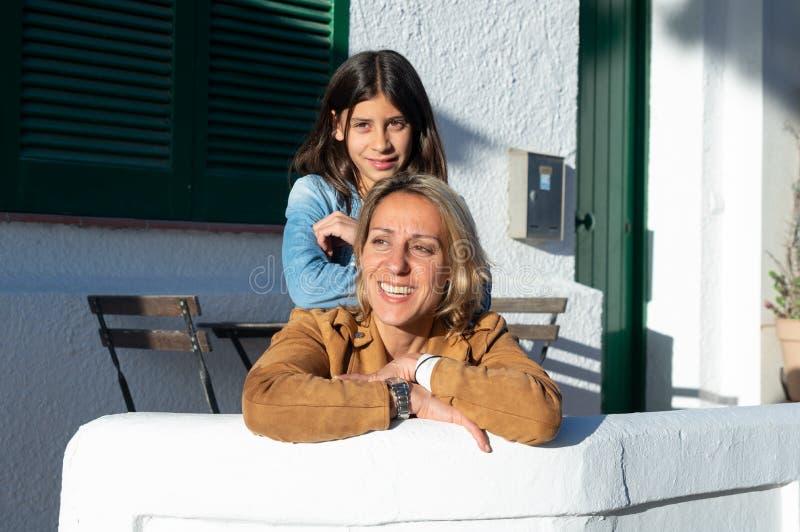 A mãe e a filha abraçaram no por do sol em uma vila mediterrânea com paredes brancas foto de stock