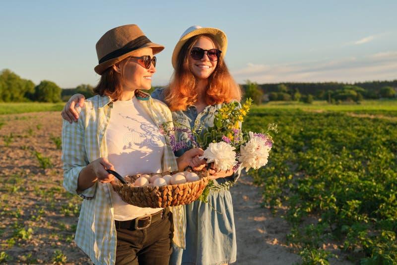 Mãe e filha adolescente com uma cesta de ovos frescos no jardim, hora dourada fotografia de stock royalty free