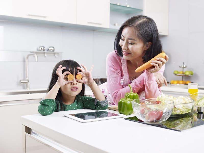 Mãe e filha asiáticas na cozinha fotografia de stock royalty free