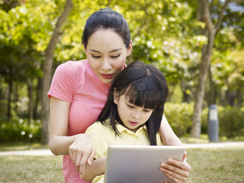 Mãe e filha asiáticas que usa o tablet pc imagem de stock royalty free