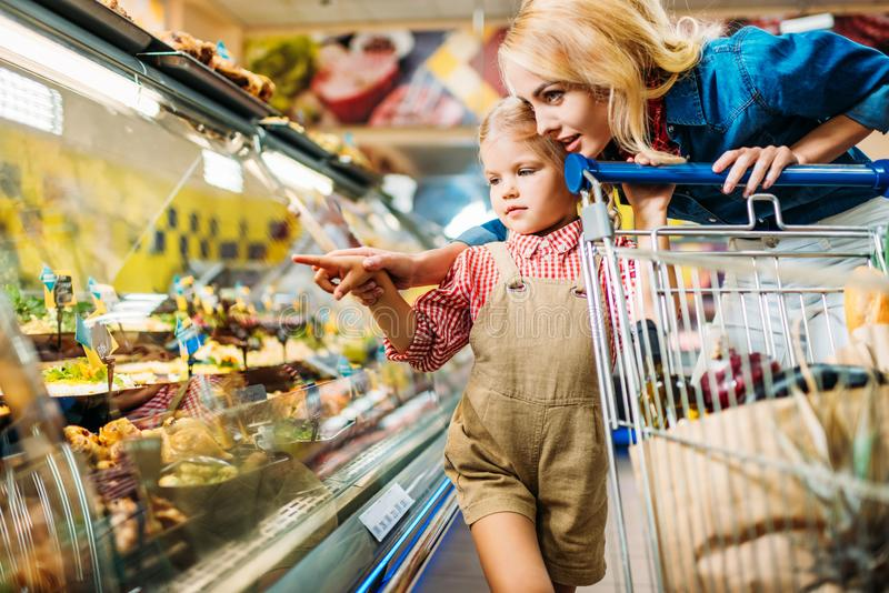 mãe e filha bonitas com o trole da compra que escolhe o alimento ao comprar imagem de stock royalty free