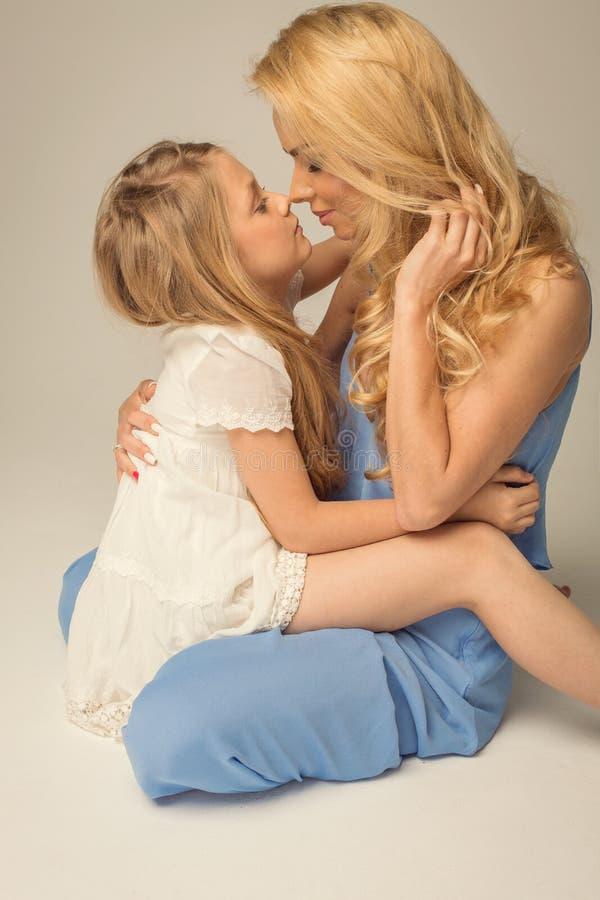 A mãe e a filha bonitas estão tocando delicadamente nos narizes fotos de stock