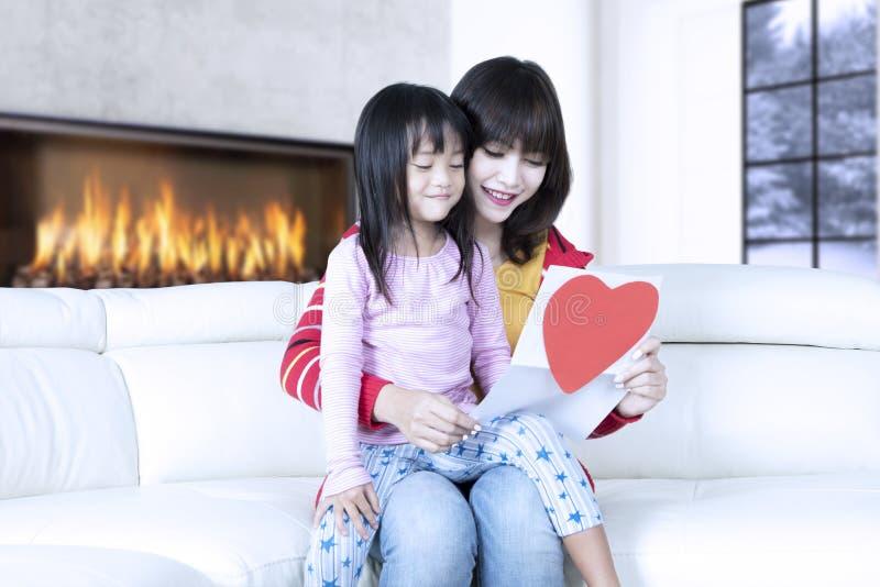 A mãe e a filha bonitas guardam a letra fotos de stock