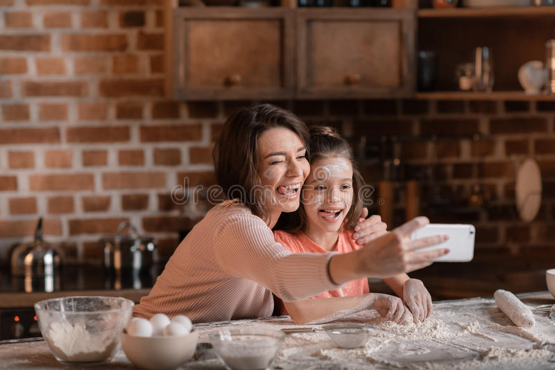 Mãe e filha com farinha nas caras que tomam o selfie fotos de stock