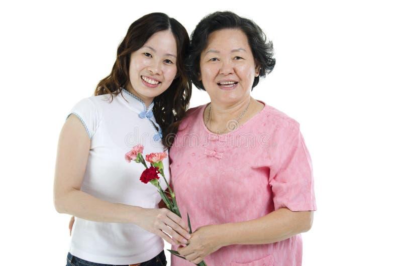 Mãe e filha com flor do cravo fotografia de stock