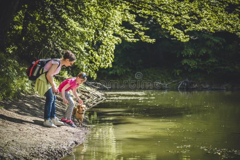 Mãe e filha com o cão pelo lago imagem de stock royalty free