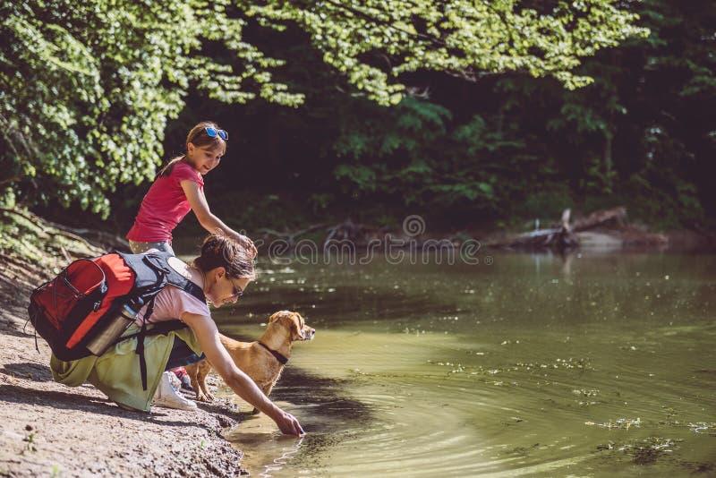Mãe e filha com o cão pelo lago fotografia de stock