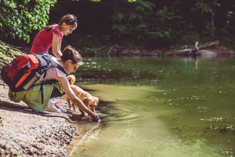 Mãe e filha com o cão pelo lago fotos de stock