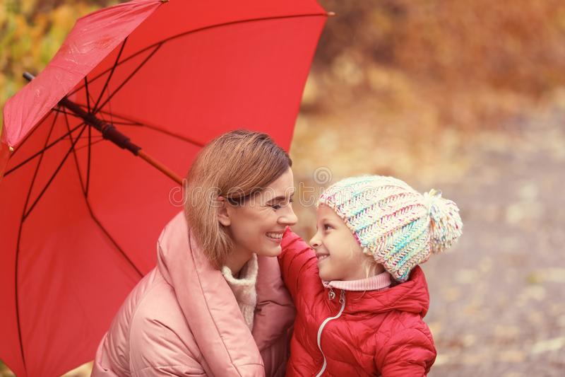 Mãe e filha com o guarda-chuva no parque do outono fotografia de stock royalty free