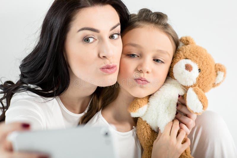 Mãe e filha com o urso de peluche que toma o selfie com smartphone fotos de stock