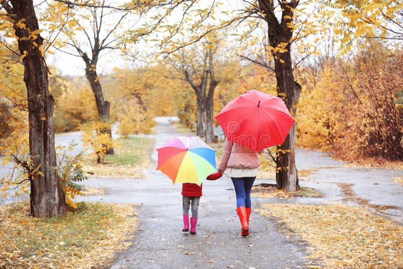 Mãe e filha com os guarda-chuvas que tomam a caminhada no parque do outono imagem de stock royalty free