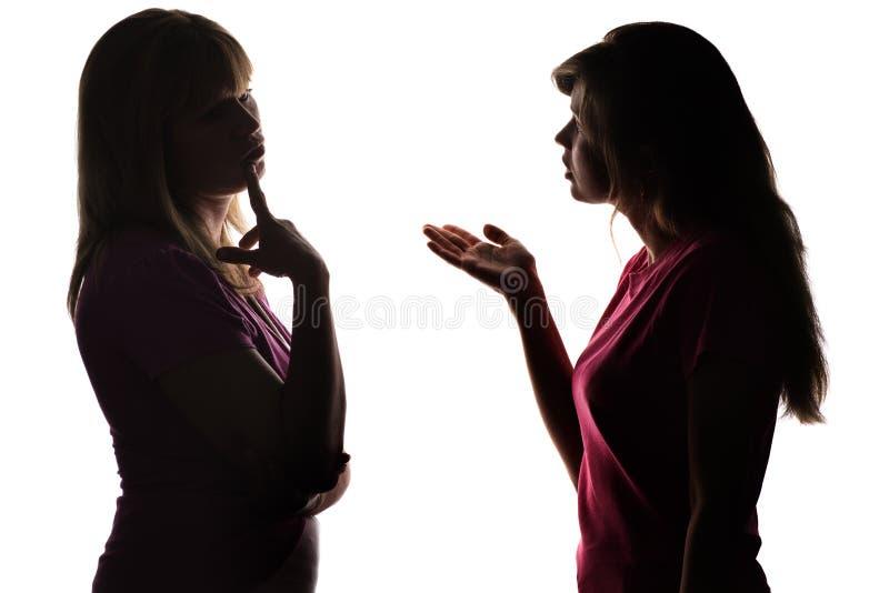 A mãe e a filha da silhueta dialogam, pai pensam que decisão a tomar fotografia de stock royalty free