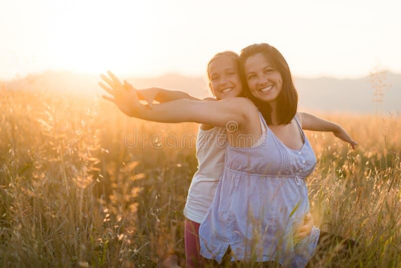 Mãe e filha de sorriso despreocupadas no campo no por do sol imagens de stock