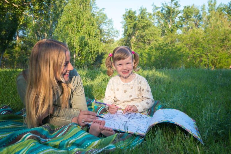A mãe e a filha de sorriso estão pintando em um livro no parque fotos de stock