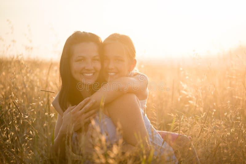 Mãe e filha de sorriso que abraçam-se foto de stock royalty free