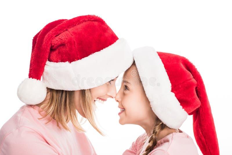 Mãe e filha de sorriso que vestem os chapéus de Santa que tocam nos narizes, foto de stock