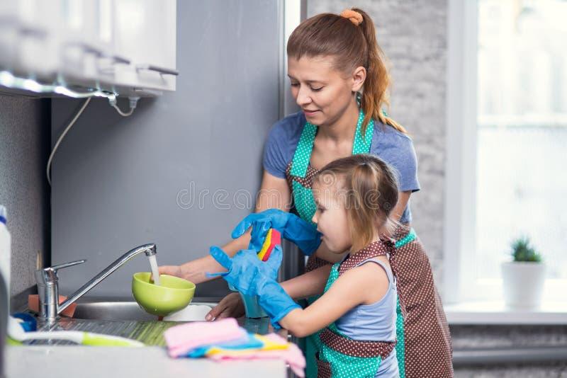 Mãe e filha em casa nos pratos de lavagem da cozinha fotografia de stock