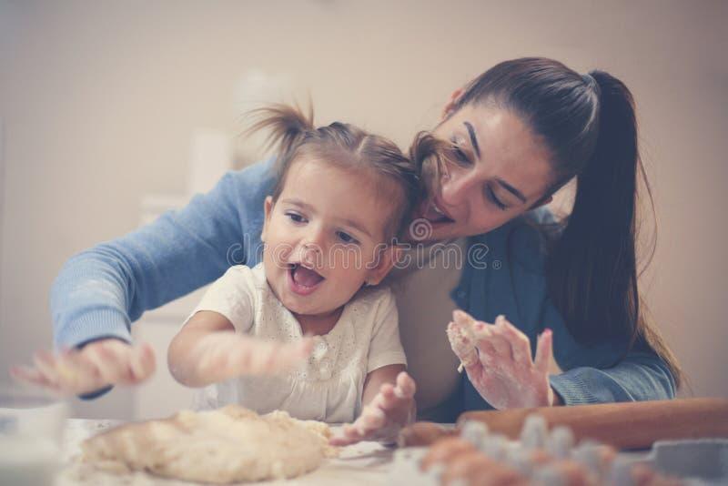 Mãe e filha em casa que fazem a massa para a cookie e o p imagens de stock