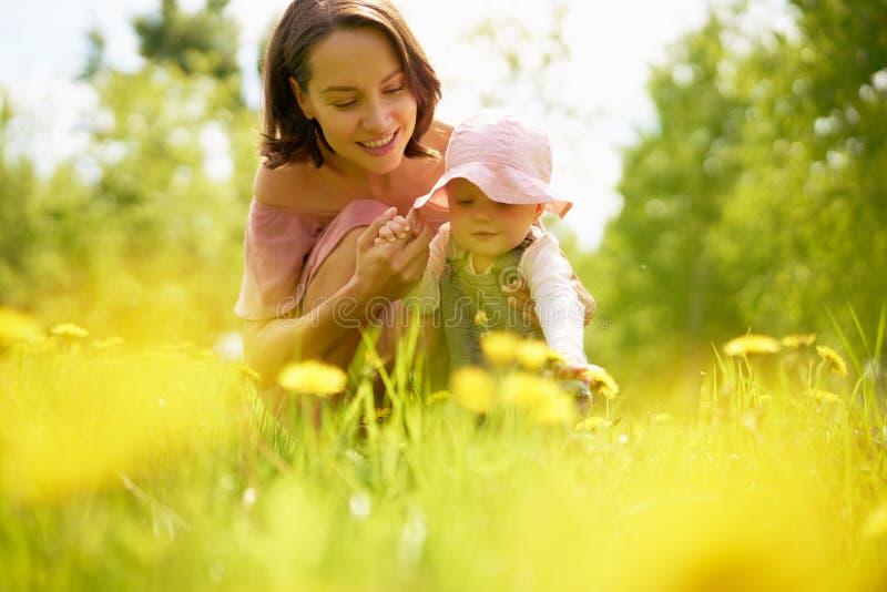 Mãe e filha em um prado com dentes-de-leão fotografia de stock royalty free