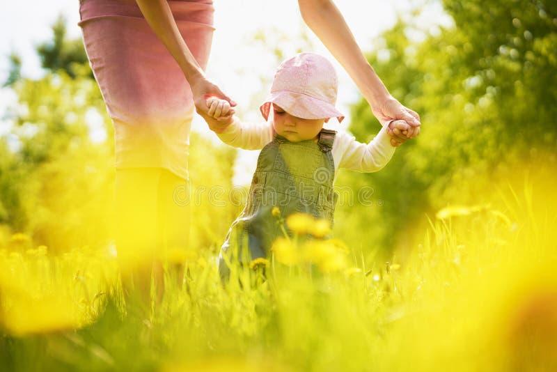 Mãe e filha em um prado com dentes-de-leão fotos de stock