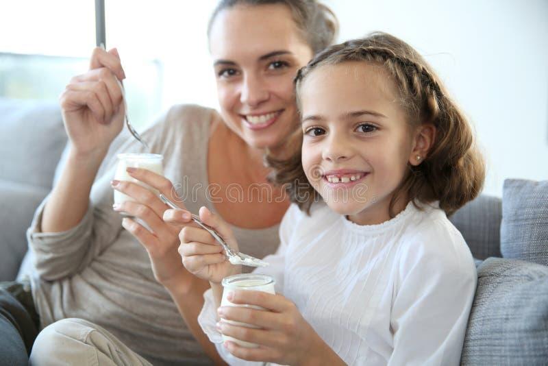 Mãe e filha felizes com youghurt fotos de stock royalty free