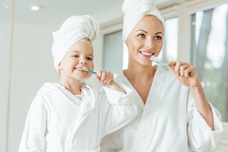 mãe e filha felizes na escovadela dos roupões e das toalhas imagens de stock royalty free