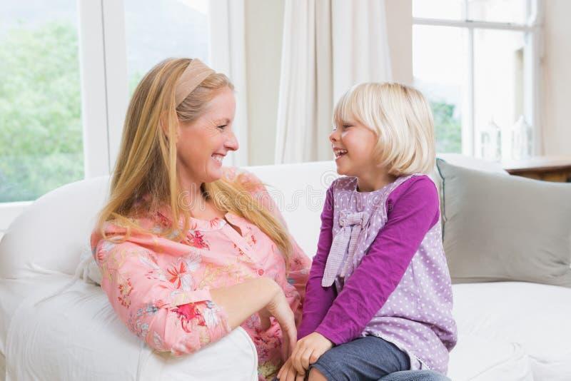Mãe e filha felizes no sofá fotos de stock royalty free