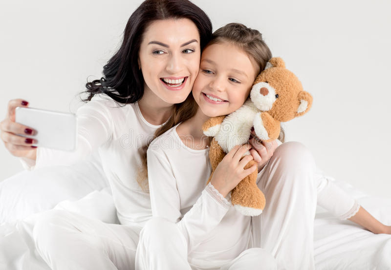 Mãe e filha felizes nos pijamas que tomam o selfie com smartphone foto de stock royalty free