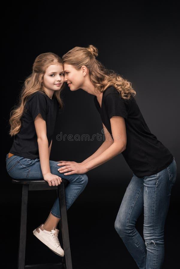 Mãe e filha felizes nos t-shirt pretos que levantam junto imagem de stock
