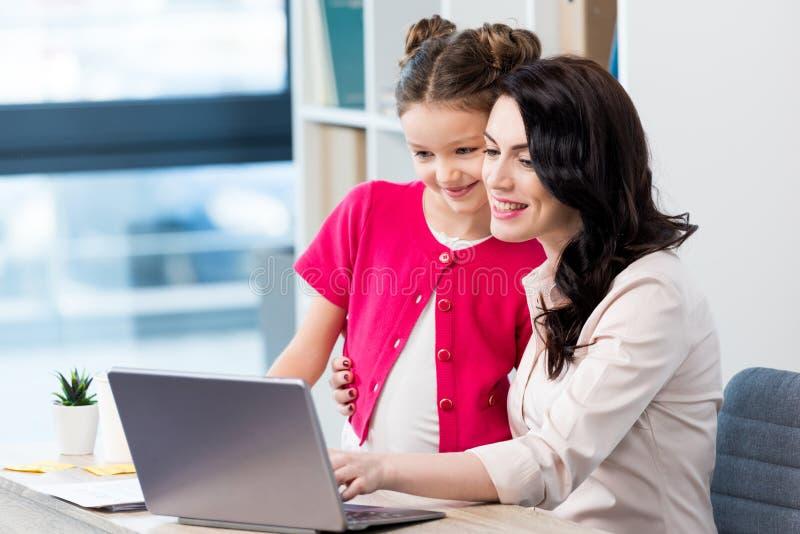 Mãe e filha felizes que usa o portátil no local de trabalho imagem de stock