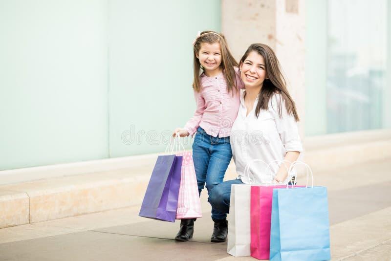 Mãe e filha latino-americanos com sacos de compras imagens de stock