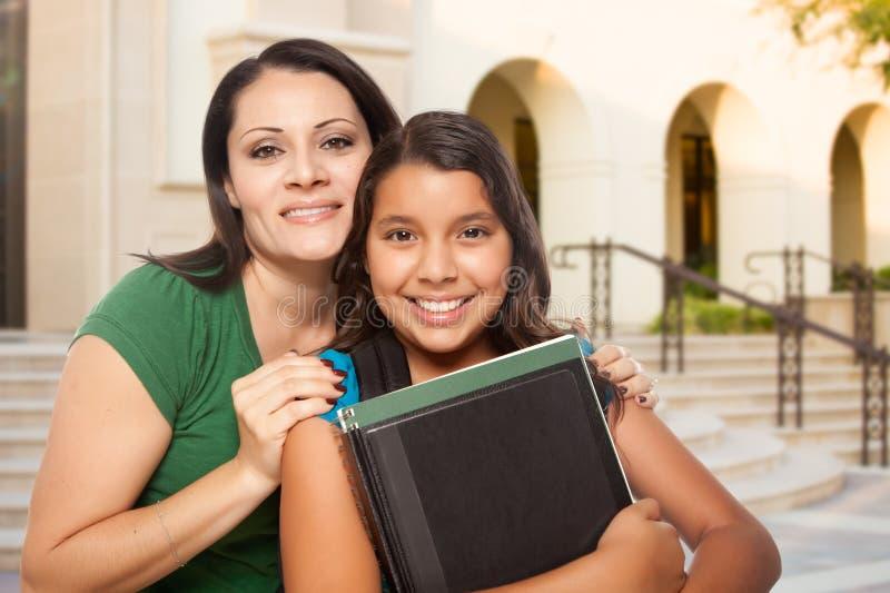 Mãe e filha latino-americanos orgulhosas no terreno na escola fotos de stock