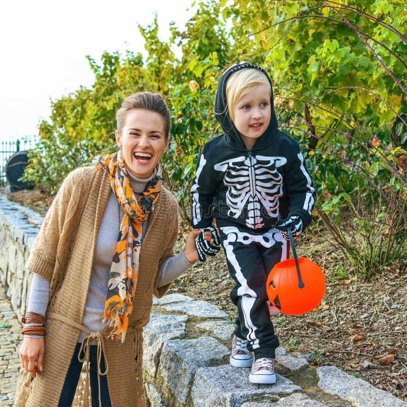 Mãe e filha modernas de sorriso em Dia das Bruxas no jogo do parque fotos de stock