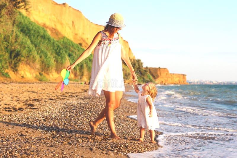Mãe e filha na praia no por do sol imagem de stock