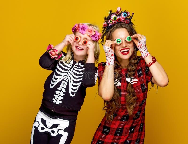 A mãe e a filha no Dia das Bruxas trajam ter o tempo do divertimento fotos de stock