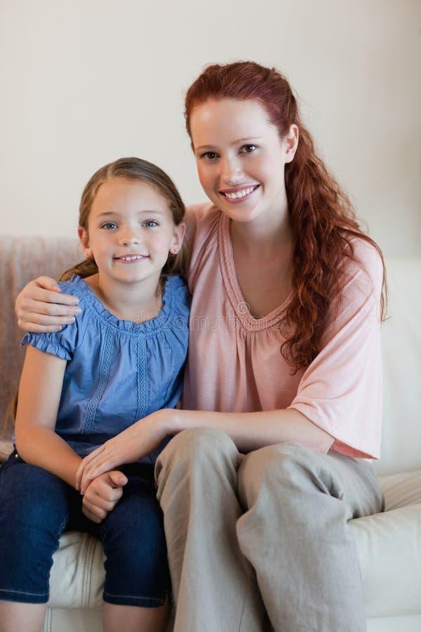 Mãe e filha no sofá fotografia de stock royalty free