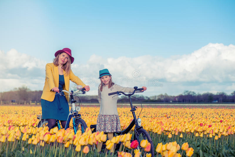 A mãe e a filha no tulipas amarelas colocam imagens de stock royalty free