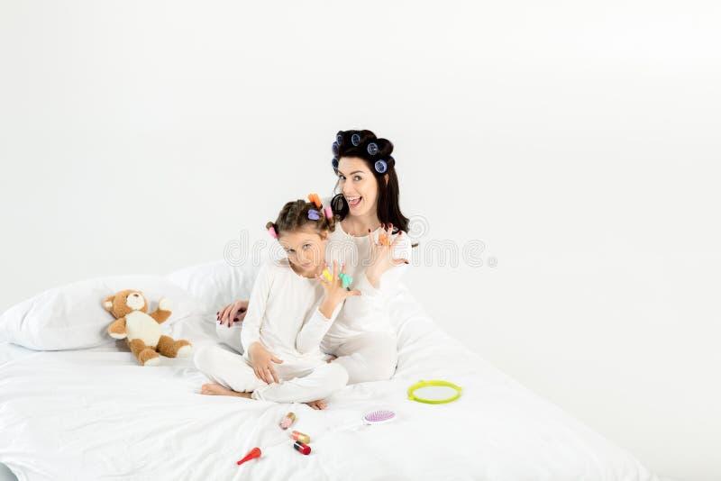 Mãe e filha nos encrespadores e nos pijamas que sentam-se na cama e que sorriem na câmera fotos de stock