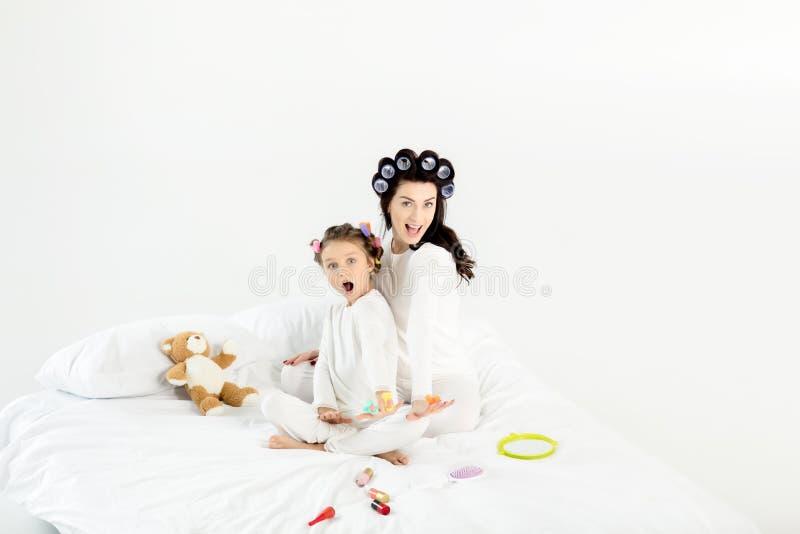 Mãe e filha nos encrespadores e nos pijamas que têm o divertimento na cama imagens de stock royalty free