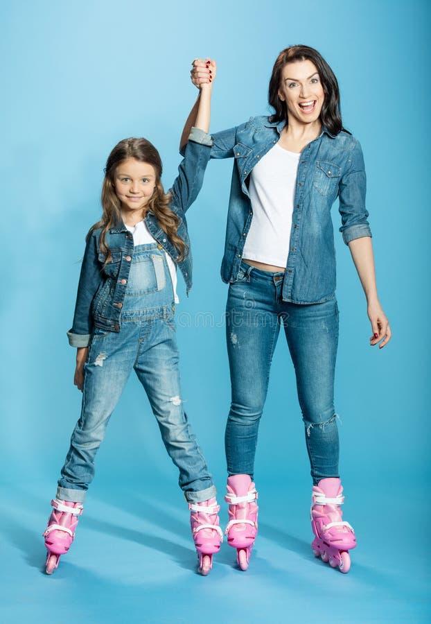 Mãe e filha nos patins de rolo que guardam as mãos no estúdio fotografia de stock royalty free