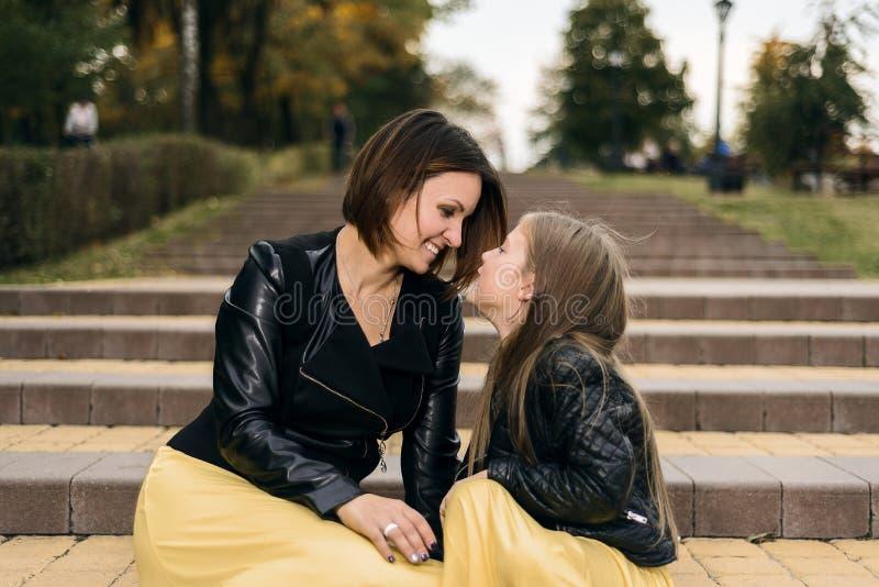A mãe e a filha olham junto se e casam-se sentam-se nas escadas no parque Dia do `s da matriz fotografia de stock