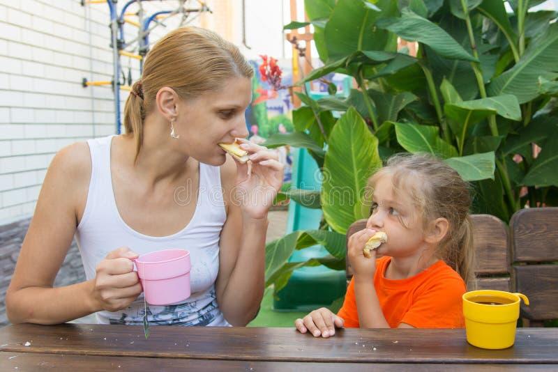A mãe e a filha olharam se que come o café da manhã na varanda imagens de stock royalty free