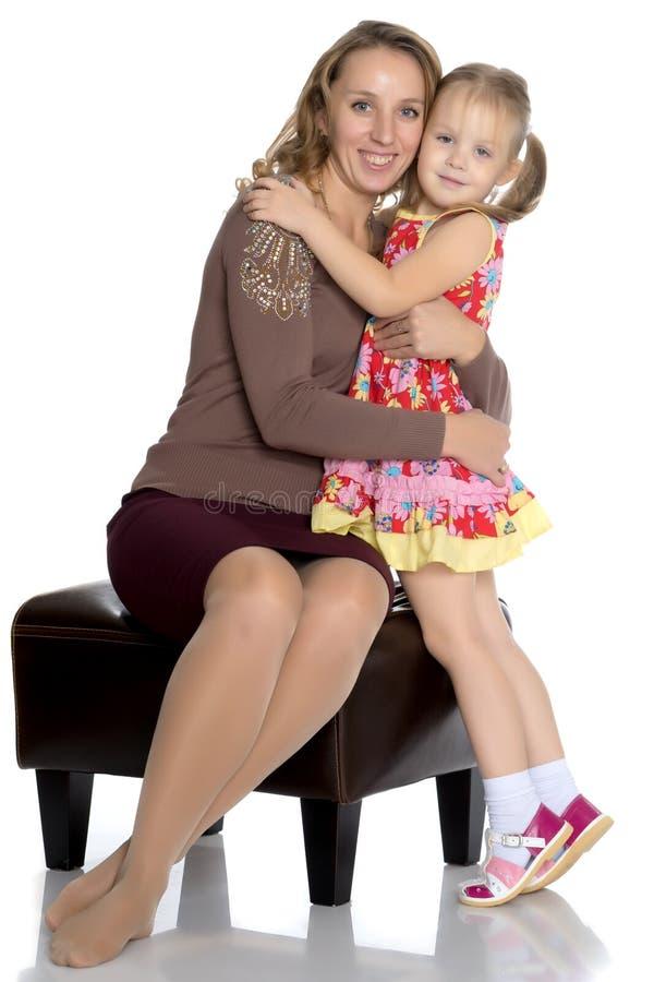 A mãe e a filha pequena abraçam delicadamente foto de stock royalty free